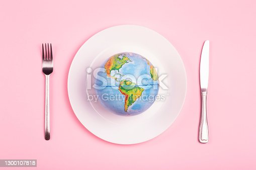 Globe on a plate for food on a pink background. Power, economy, politics, globalism, hunger, poverty and world food concept.
