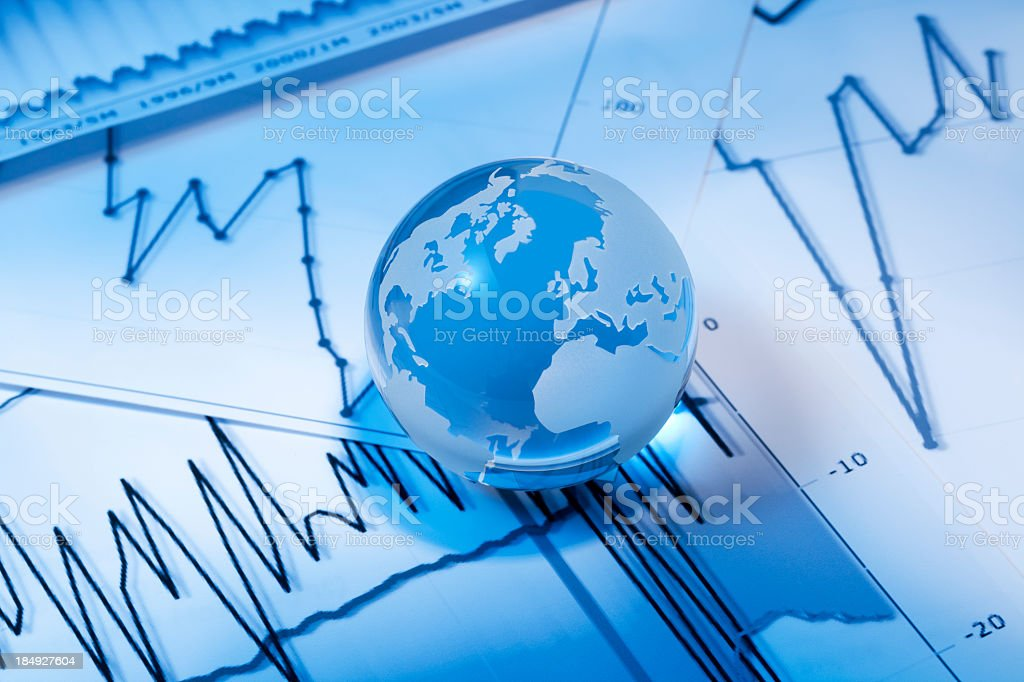 A globe on top of financial papers stock photo