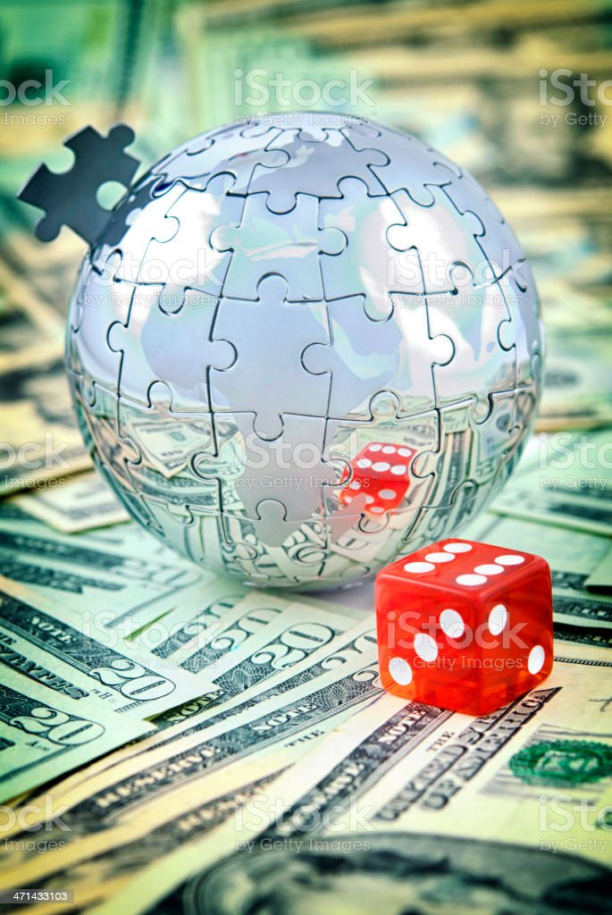 Globe puzzle and dice on US dollars royalty-free stock photo