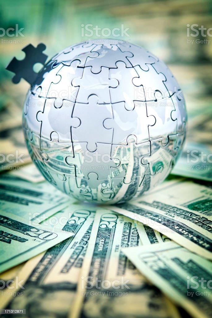 Globe puzzle on US dollars stock photo