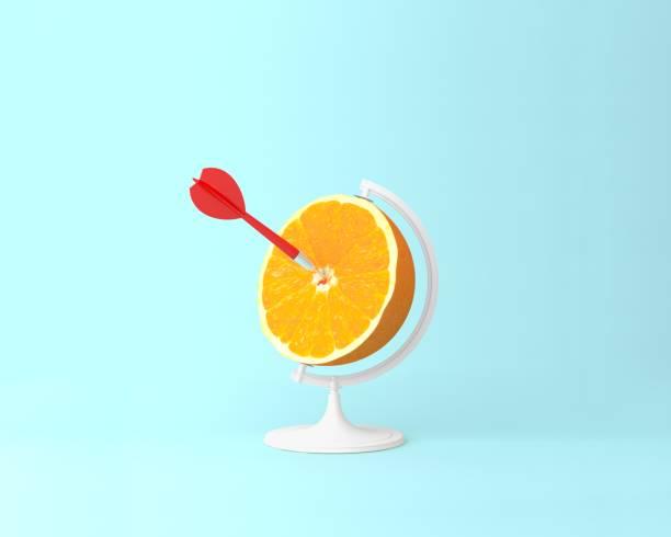 kugel kugel kugel, frischen orangenscheibe mit roten pfeil obst konzept auf pastell blau hinterlegt. minimale idee geschäftskonzept. idee kreativ arbeiten innerhalb einer werbung marketing kommunikation - target raumgestaltung stock-fotos und bilder