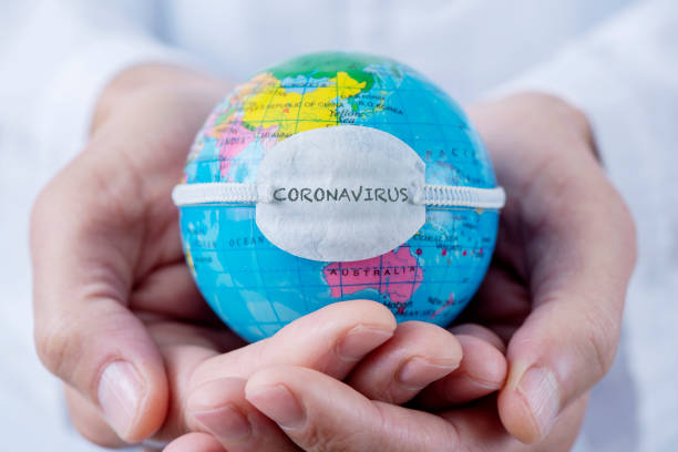 globe with a mask and text coronavirus closeup of a caucasian doctor man holding a world globe with a protective mask with the word coronavirus written in it covid mask stock pictures, royalty-free photos & images