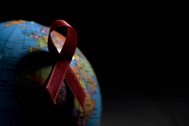 globe with a red ribbon for the fight against AIDS stock photo