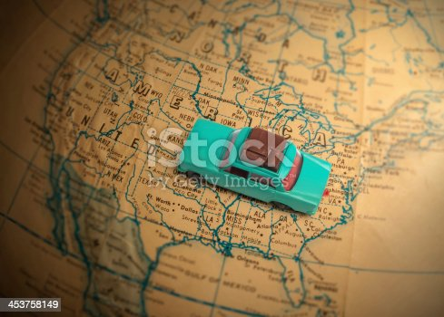 Toy car with luggage on a vintage globe map of the United States with a shallow depth of field.