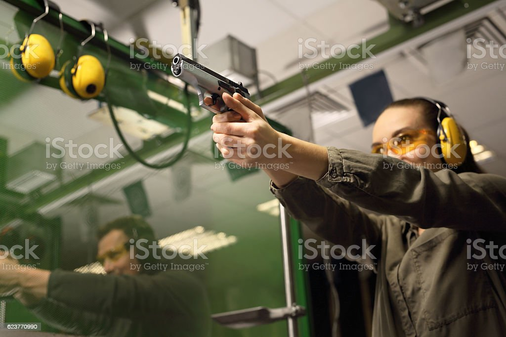 Glock, woman shoots at the shooting range stock photo