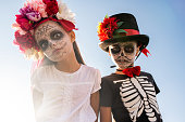 istock Gloomy and scary halloween boy and girl with painted faces looking at you 1273306724