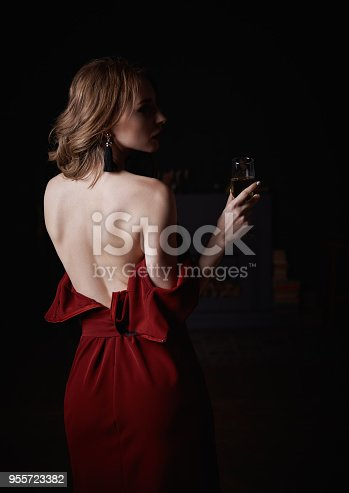 istock Gloomy mysterious portrait of alluring beautiful young woman in downcast red dress with goblet of champagne in hand. Rear view 955723382