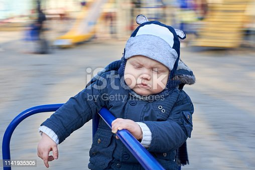 istock A gloomy pensive little boy rides a merry-go-round on the playground 1141935305