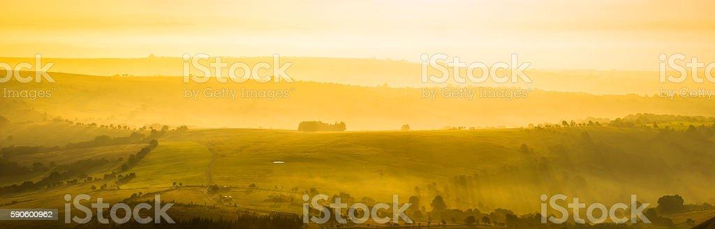 Glorious golden sunrise over idyllic rural hills summer pasture panorama stock photo