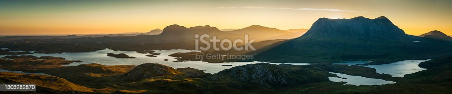Golden rays of sunlight streaming through the glen to illuminate the remote mountain wilderness, lochs and landscapes of Sutherland in the north west highlands of Scotland, UK in this glorious daybreak panorama.