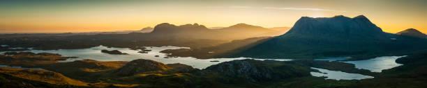 Glorious mountain sunrise golden dawn peaks panorama Inverpolly Highlands Scotland stock photo