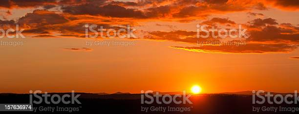 Photo of Glorious sunset dramatic cloudscape over forest and mountain peaks panorama