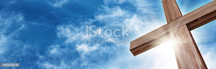 Wooden Cross with a Bright Blue Sky and Sun