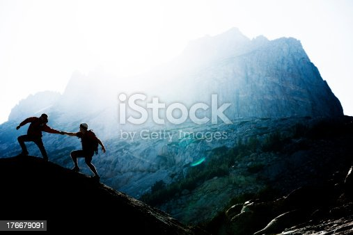 A climber helping another to the top