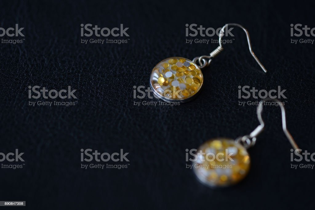 Glossy earrings made of epoxy resin with sparkles on a dark background close up stock photo