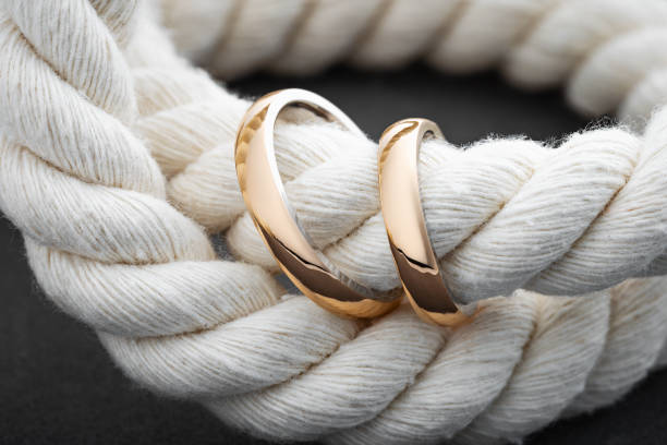 Glossy gold wedding rings on gray background with rope
