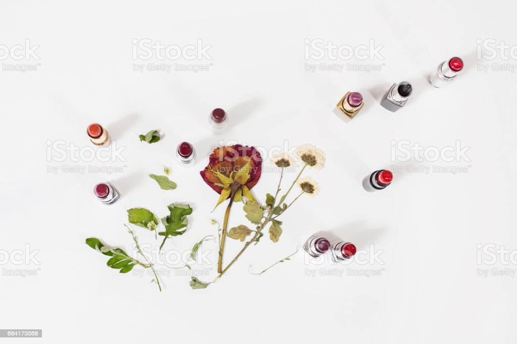 Glossy lipstick on white background. Decorative cosmetics for lips. Dried flowers on a light surface. View from above . Dry rose. royaltyfri bildbanksbilder