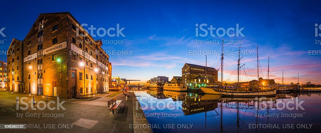 Gloucester Docks redeveloped warehouses boatyard sailing ships canal sunset panorama stock photo