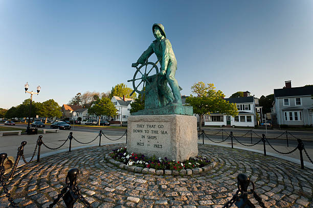 Gloucester Fisherman's Memorial Gloucester, MA, USA - May 25, 2009: The Gloucester Fisherman\'s Memorial is a well-known symbol of Gloucester and of the fishing industry. This bronze statue of a fisherman looks out over Gloucester Harbor. gloucester massachusetts stock pictures, royalty-free photos & images