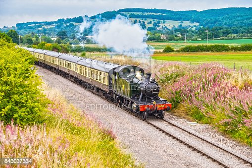 Steam locomotive pulling out of a station- gorgeous English countryside background