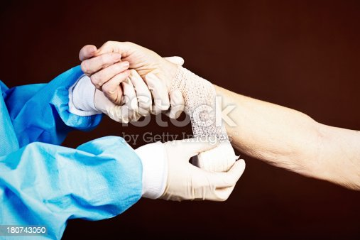 istock Gloved and gowned medical professional dresses elderly patient's arm 180743050