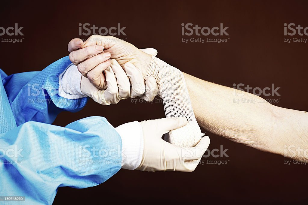 Gloved and gowned medical professional dresses elderly patient's arm stock photo