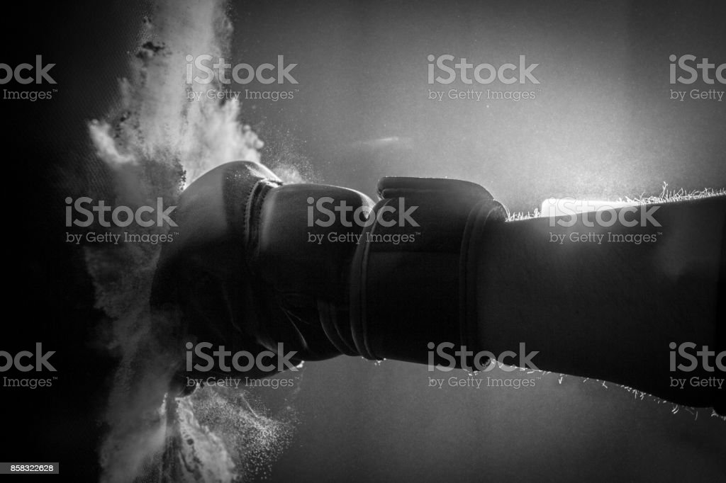 Gloved Fist Hitting a Punching Bag stock photo