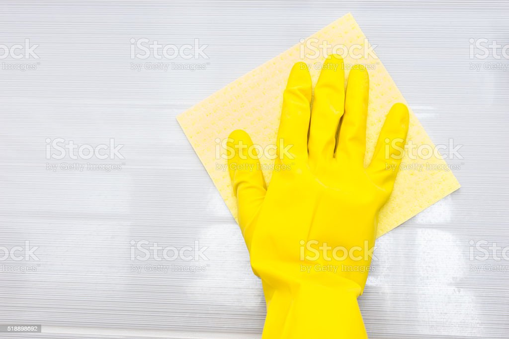 Gloved hand and rag over surface stock photo