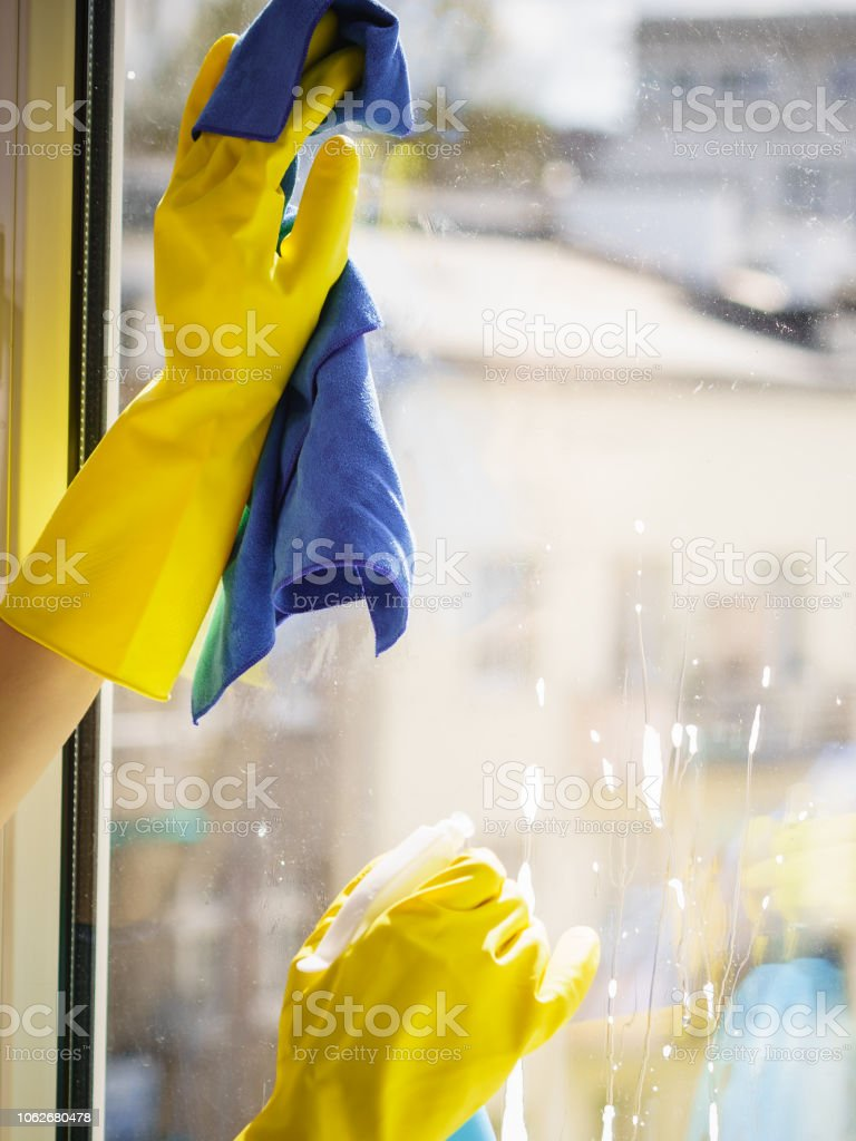 Female hand in yellow gloves cleaning window pane with rag and spray...