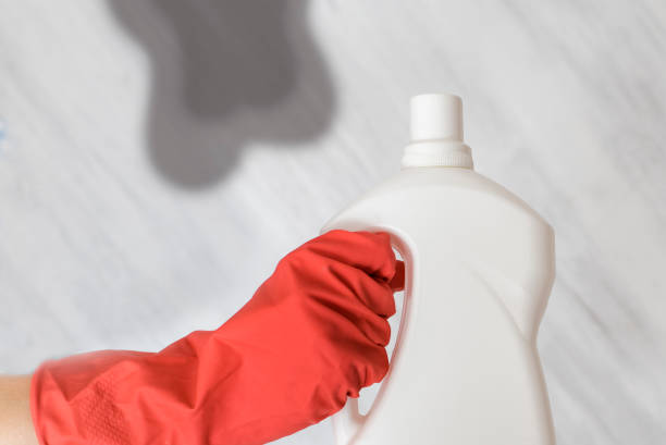 gloved hand holding a bottle of washing liquid. spot on background - bleach stock pictures, royalty-free photos & images