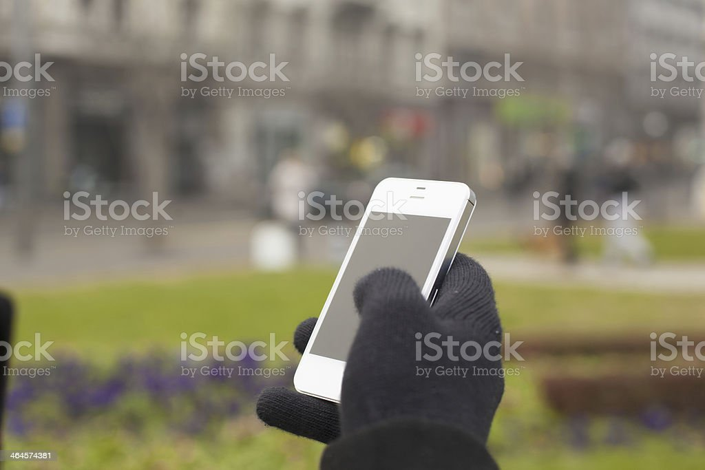 Gloved hand holding phone with blurred background stock photo