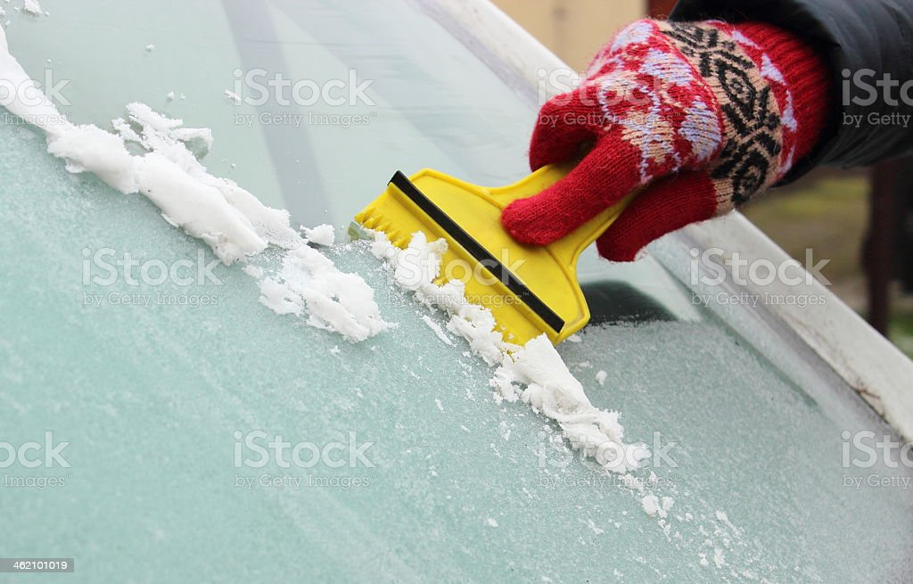 Gloved hand scraping ice from car windshield stock photo