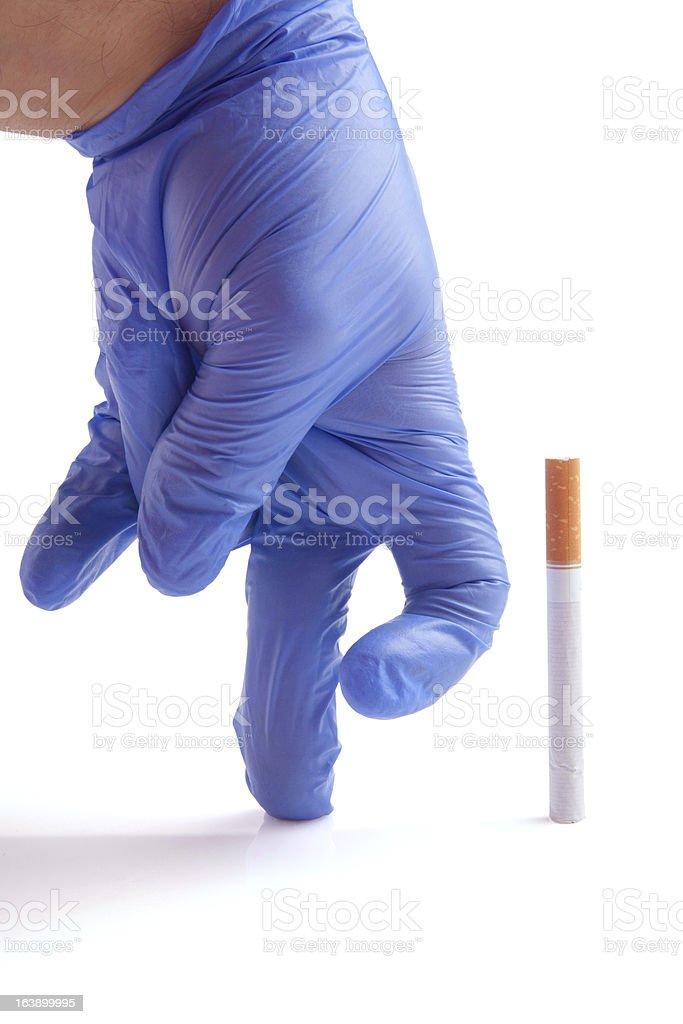 Gloved hand throwing cigarette Quit smoking metaphor stock photo
