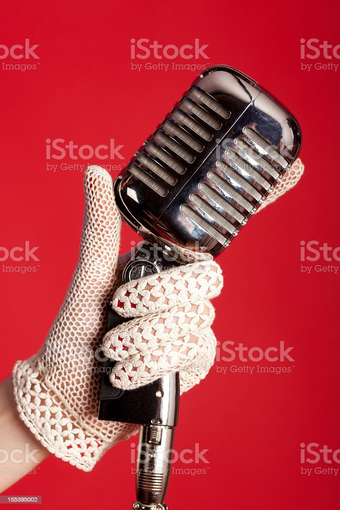 Gloved hand with vintage microphone stock photo