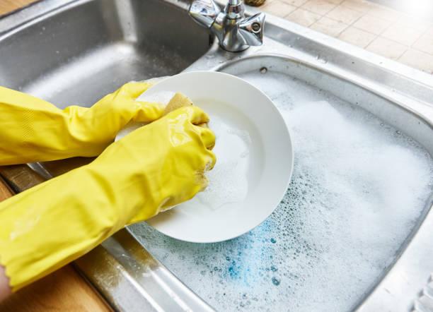 Gehandschoende handen afwas de in de aanrecht. foto