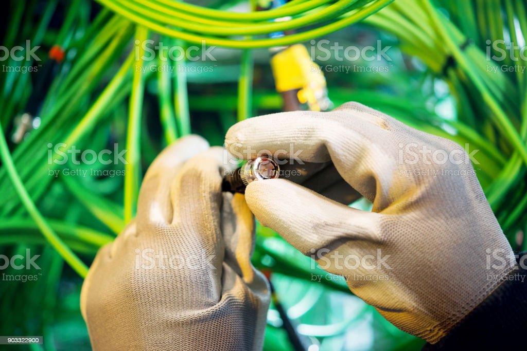 Ein behandschuhte Arbeiter prüft den Stecker des video auf dem server – Foto