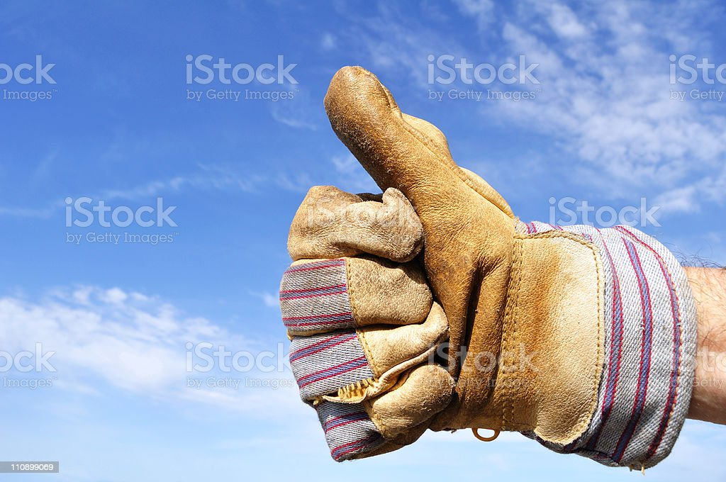 Gloved working hand giving a thumbs up sign  stock photo