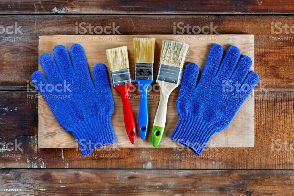 Gloves and brushes on old wooden boards. Concept: home repair, house building stock photo