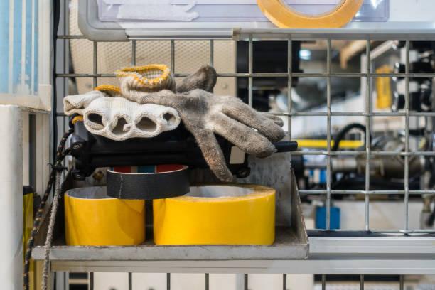 Handschuhe und Klebeband auf Regal in Fabrik Ausrüstung allgemeine industrielle – Foto