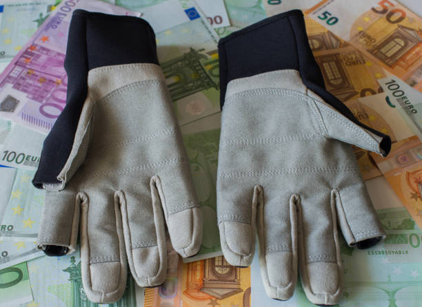 handschuhe für das segeln vor dem hintergrund der euro-banknoten. - segelhandschuhe stock-fotos und bilder