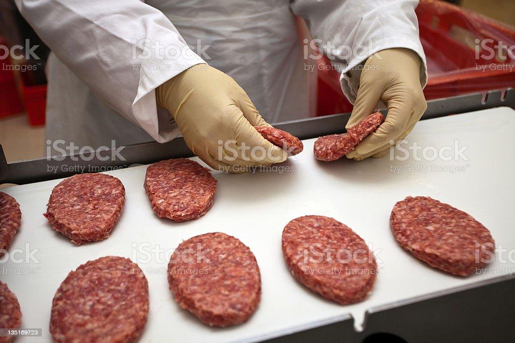 Gloves hands preparing raw hamburgers stock photo