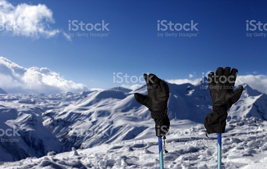 Gloves on ski poles and snowy mountain stock photo