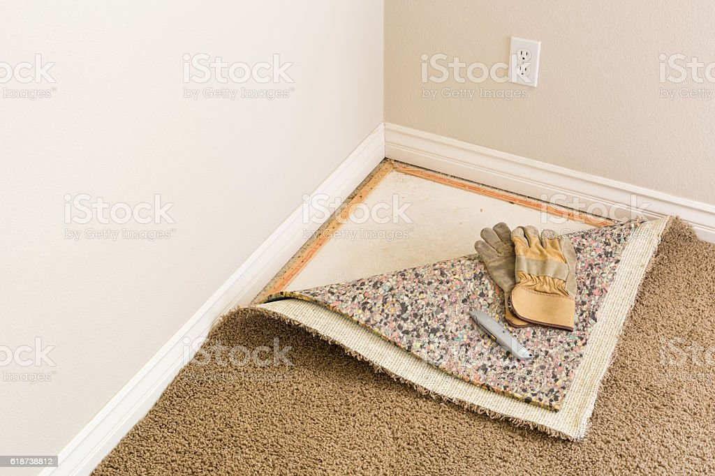 Gloves, Utility Knife On Pulled Back Carpet Pad In Room. stock photo
