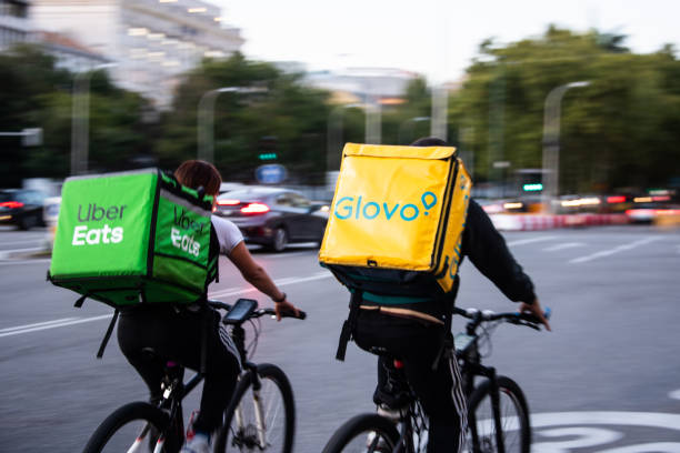 Glovo and Uber Eats delivery workers in motion in Madrid, Spain - foto stock