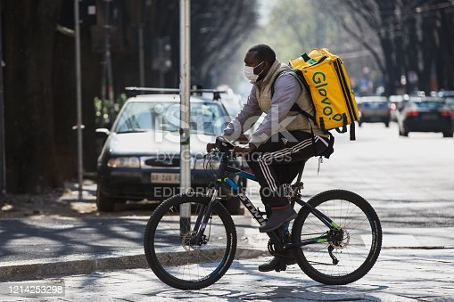 Food delivery man on bike working with protection mask during coronavirus lockdown in Italy