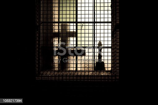 istock Glow of light through a frosted window covered with a security grille at night. 1053217394