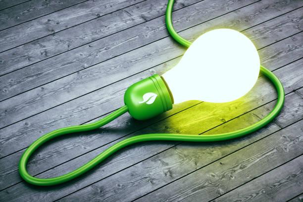 Glowing abstract green energy light bulb on hard wood floor stock photo