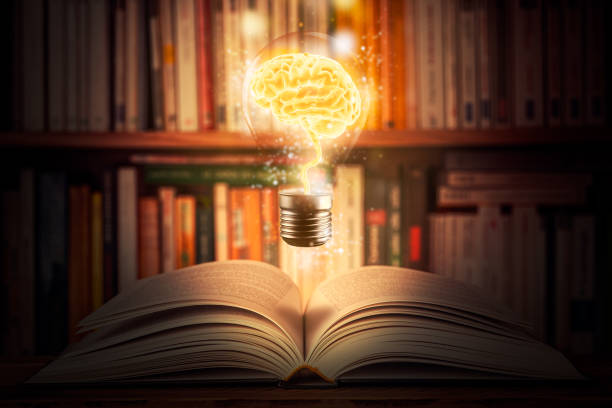 Glowing and shining brain lightbulb over an open book with a bookshelf as background. Knowledge, study, cognition, learning, literacy, library 3d illustration concepts. Mixed media. stock photo