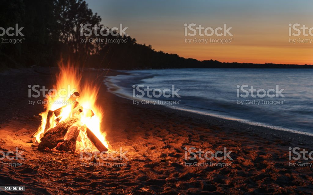 Glowing Bonfire on the Beach at Sunset stock photo