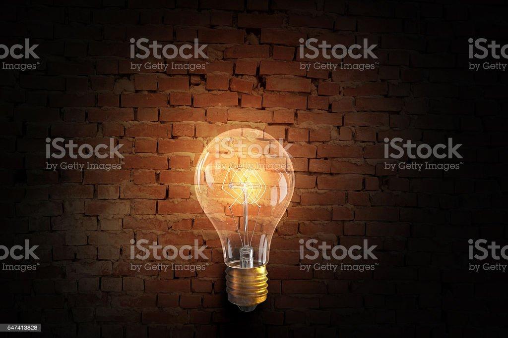 Glowing bulb on brick surface . Mixed media stock photo